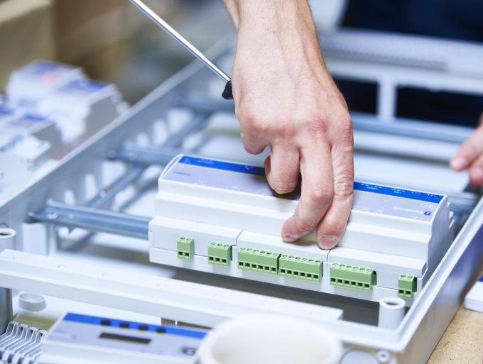 électricien-installateur plaçant un module Master DGQG02 sur un rail dans un coffret électrique
