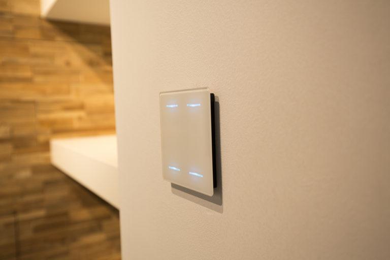 le bouton tactile DBRLCD02 sur un mur dans un intérieur de maison